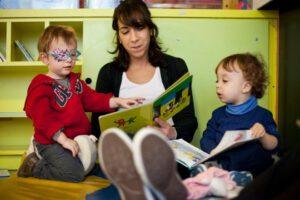 enfants en train de lire un livre avec un adulte